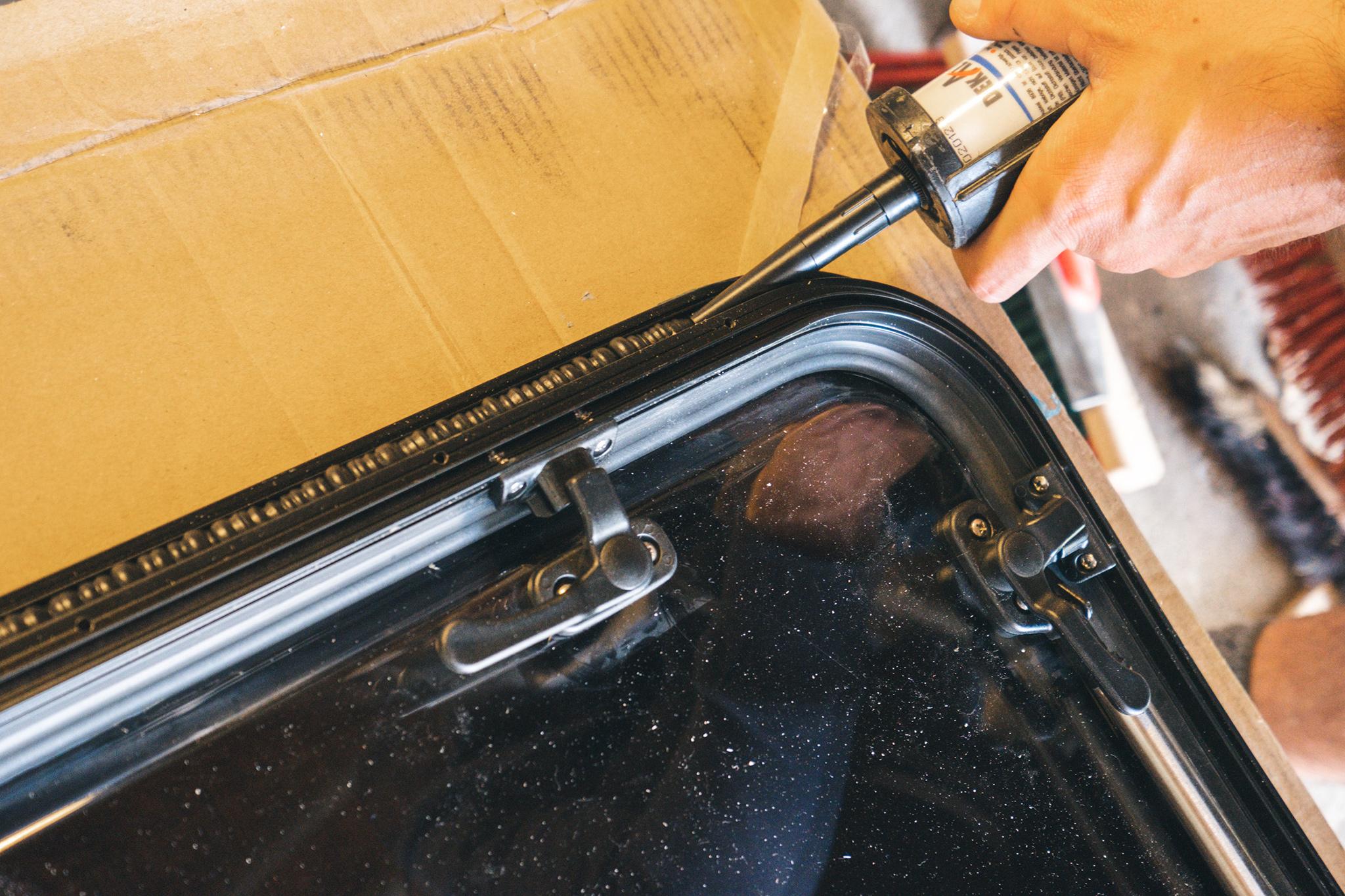 Dichtmittel wird auf das Carbest Ausstellfenster RW Van aufgetragen